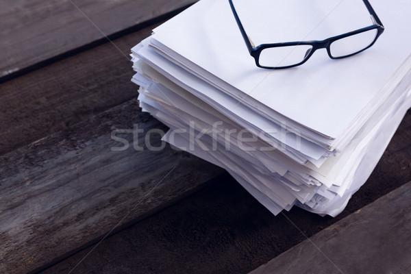 Primer plano gafas papel en blanco escritorio madera marco Foto stock © wavebreak_media