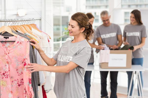Mosolyog női önkéntes választ ruházat iroda Stock fotó © wavebreak_media