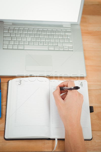 Stock photo: Man writing in diary while laptop at desk in office
