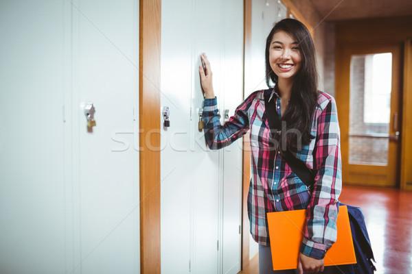 Cheerful student standing next the locker Stock photo © wavebreak_media