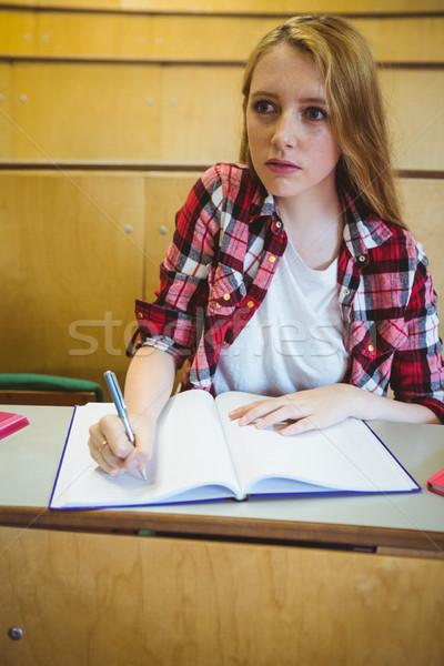 Focused student taking notes during class Stock photo © wavebreak_media