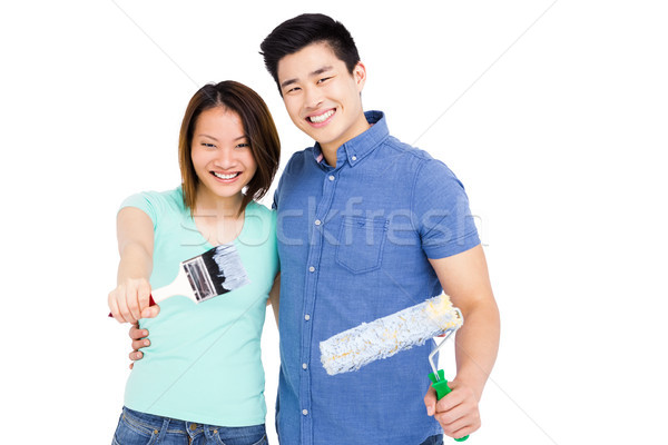 Stock photo: Young couple holding paint brush and paint roller