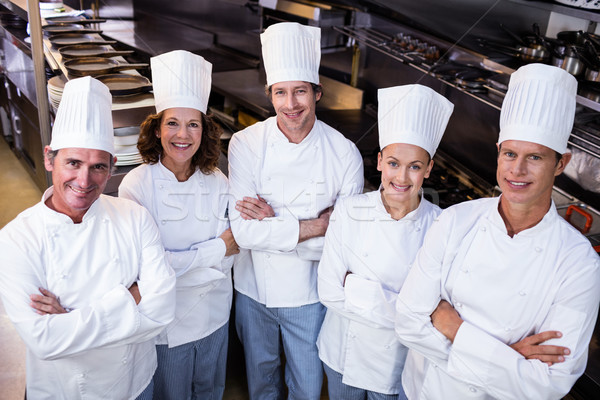 Happy chefs team standing together in commercial kitchen Stock photo © wavebreak_media
