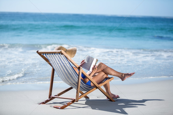 Pretty mature woman reading a book lying on deck chair Stock photo © wavebreak_media