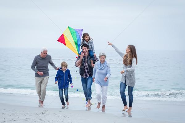 Multi-generation family running at sea shore against sky Stock photo © wavebreak_media