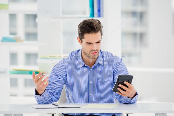 Businessman calculating accounts on a calculator Stock photo © wavebreak_media