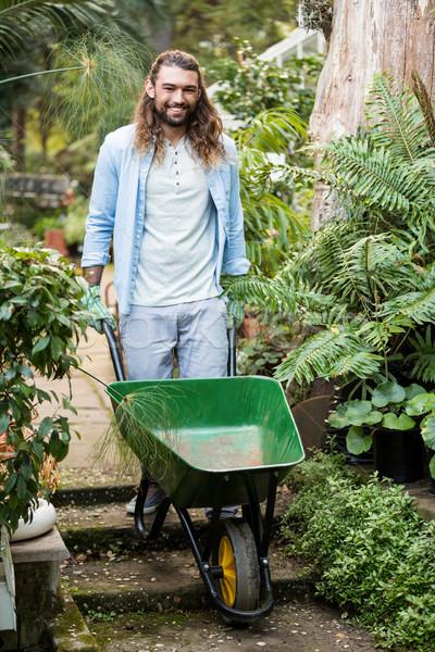 Portrait of happy gardener pushing wheelbarrow at garden Stock photo © wavebreak_media