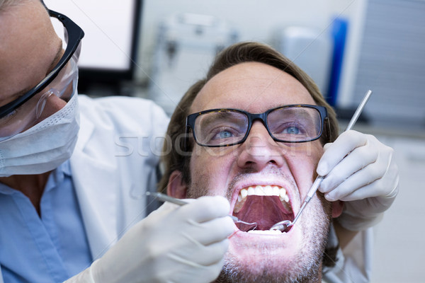 Female dentist examining male patient with tools Stock photo © wavebreak_media
