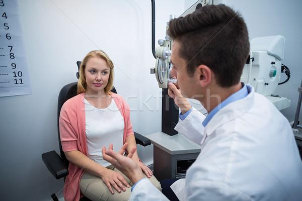 Optometrist assisting female patient Stock photo © wavebreak_media