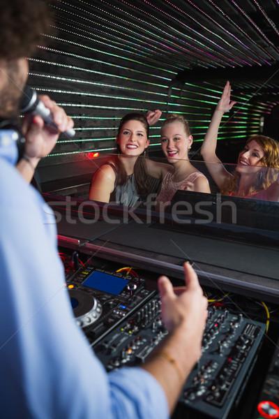 Male disc jockey playing music with three women dancing on the dance floor Stock photo © wavebreak_media