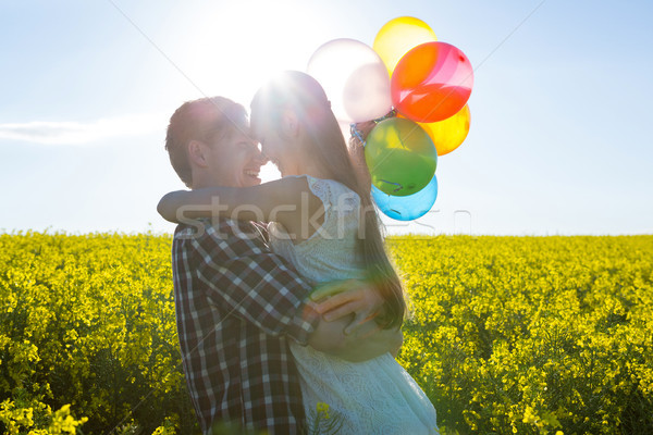 Couple holding colorful balloons and embracing each other in mustard field Stock photo © wavebreak_media