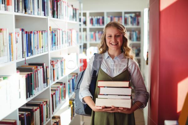 Retrato aluna em pé livros biblioteca Foto stock © wavebreak_media