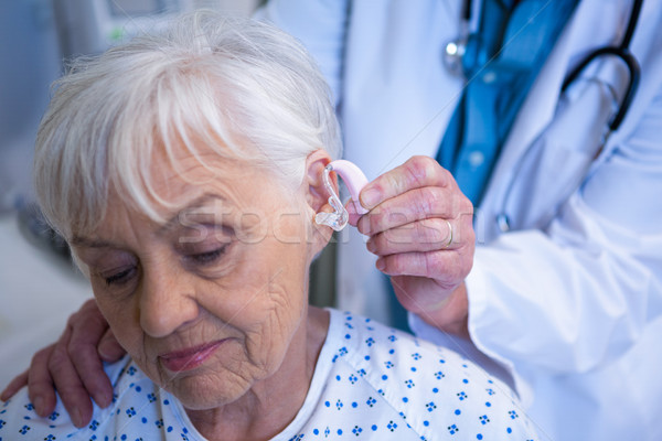 Doctor inserting hearing aid in senior patient ear Stock photo © wavebreak_media