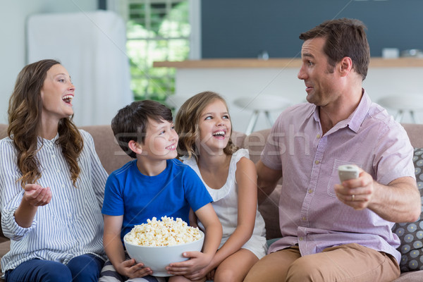 Family watching tv and eating popcorn in living room at home Stock photo © wavebreak_media