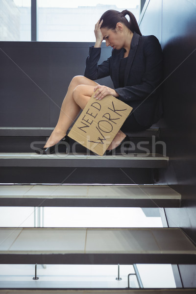 Depressed businesswoman sitting on stairs holding cardboard sheet with text need work Stock photo © wavebreak_media