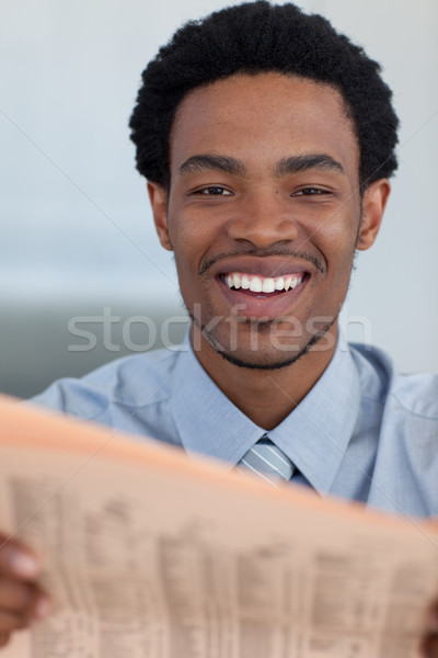 Stock photo: Attractive Afro-American businessman reading a newspaper