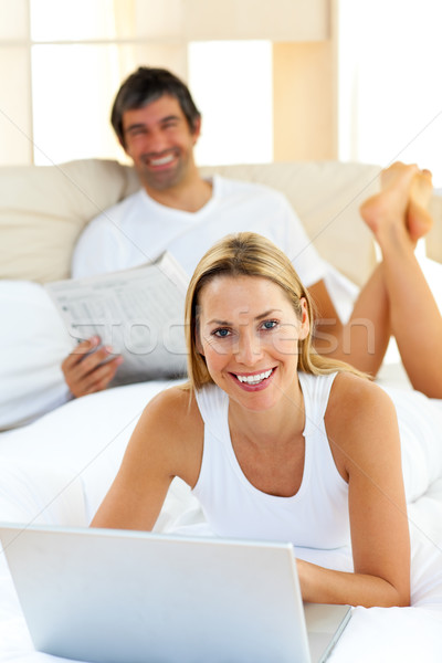 Smiling couple lying on bed using computer Stock photo © wavebreak_media