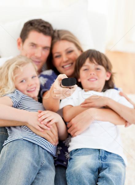 United family watching television sitting on sofa Stock photo © wavebreak_media