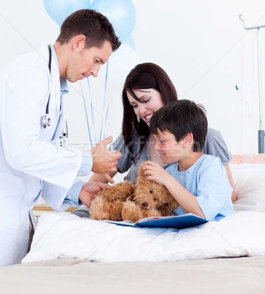 Attractive doctor playing with a little boy and his mother Stock photo © wavebreak_media
