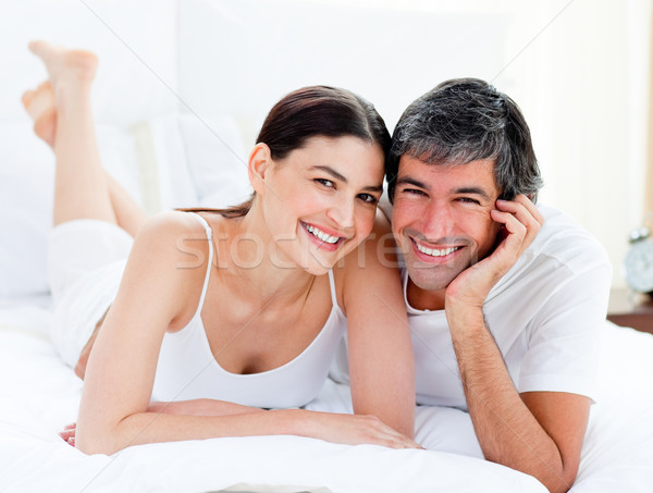 Portrait of an enamored couple embracing lying on their bed  Stock photo © wavebreak_media