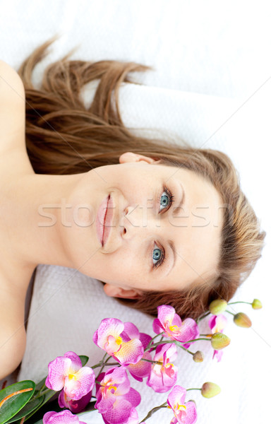 Captivating young woman lying on a massage table with flowers in a spa center Stock photo © wavebreak_media