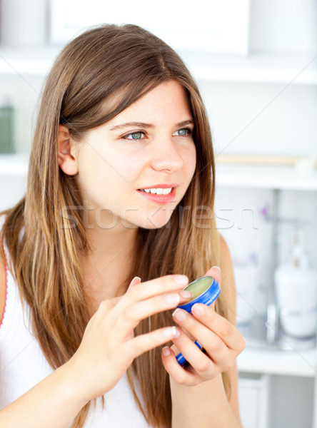 Positive woman putting make-up on her face in the bathroom Stock photo © wavebreak_media