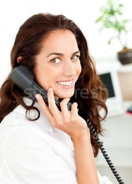 Lively young businesswoman talking on phone sitting at her desk Stock photo © wavebreak_media