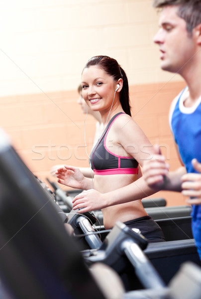 Cute athletic woman with earphones exercising on a running machine in a fitness center Stock photo © wavebreak_media
