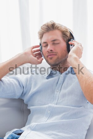 thoughful man listening music looking the top sitting in the sofa at home Stock photo © wavebreak_media