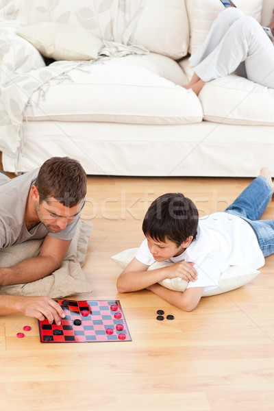 Father and son playing checkers together lying on the floor Stock photo © wavebreak_media
