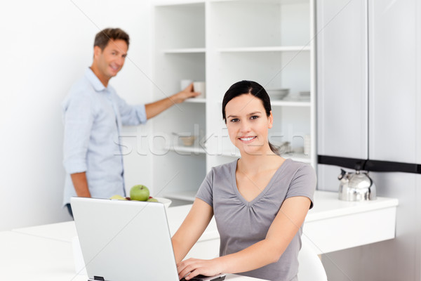 Happy woman on the laptop while her husband preparing coffee in the background Stock photo © wavebreak_media
