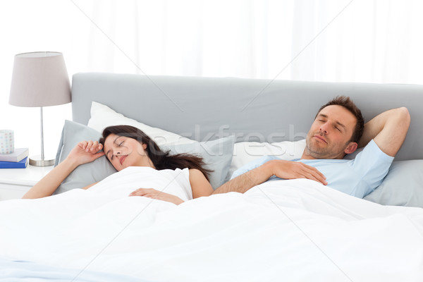Serene couple sleeping on their bed in the morning at home Stock photo © wavebreak_media
