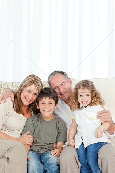 счастливая семья диван глядя камеры домой семьи Сток-фото © wavebreak_media
