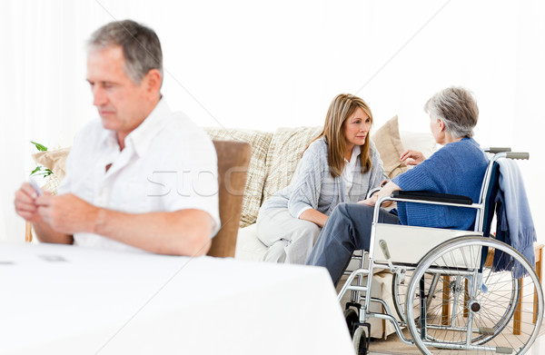 Woman talking with her friend while her husband is looking at something in a livingroom Stock photo © wavebreak_media