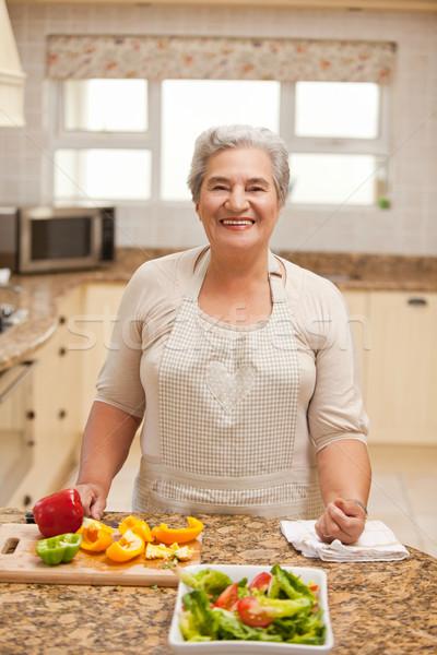 Aposentados mulher olhando câmera cozinha casa Foto stock © wavebreak_media