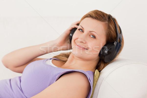 Gyönyörű nő zenét hallgat kanapé nappali mosoly Stock fotó © wavebreak_media
