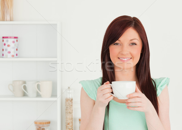 Charming red-haired woman having her breakfast in the kitchen in her appartment Stock photo © wavebreak_media