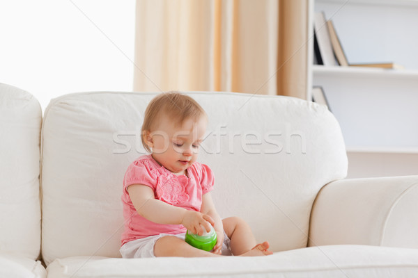 Cute blond baby playing with a ball while sitting on a sofa in the living room Stock photo © wavebreak_media