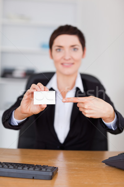 Portrait of a secrertary pointing at a blank business card in her office Stock photo © wavebreak_media