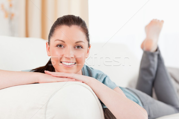 Stock photo: Attractive woman posing while lying on a sofa in the living room