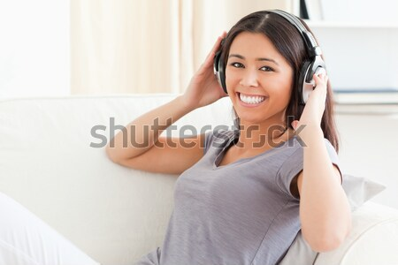 smiling woman with closed eyes and earphones in livingroom Stock photo © wavebreak_media