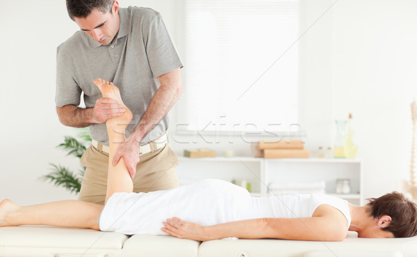 A female customer's leg is massaged by a masseur in his surgery Stock photo © wavebreak_media