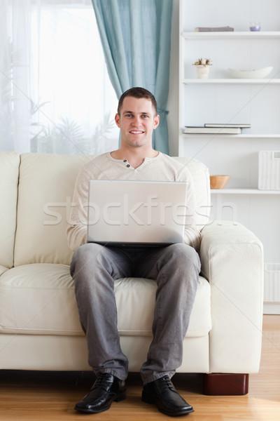 Stok fotoğraf: Portre · adam · dizüstü · bilgisayar · kullanıyorsanız · oturma · kanepe · oturma · odası