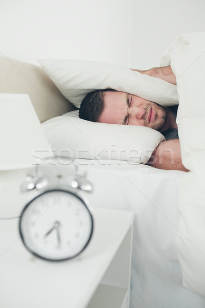 Portrait of a unhappy man covering his ears while his alarm clock is ringing in his bedroom Stock photo © wavebreak_media