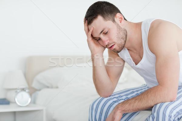 Fáradt fiatalember ül ágy másfelé néz kamera Stock fotó © wavebreak_media