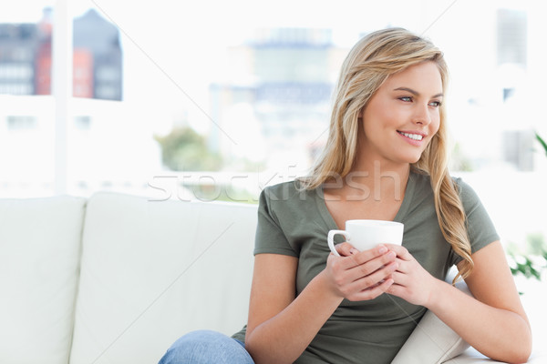 A woman smiling as she holds a cup in her hands while she sits on the couch looking to the side. Stock photo © wavebreak_media