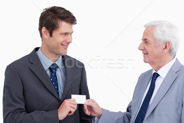 Close up of businessmen exchanging business card against a white background Stock photo © wavebreak_media