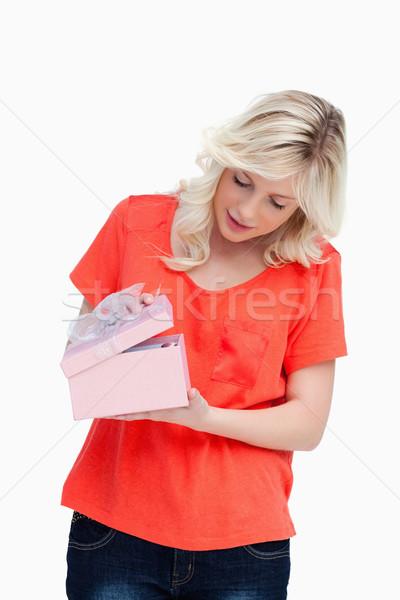 Fair-haired teenager opening her gift against a white background Stock photo © wavebreak_media