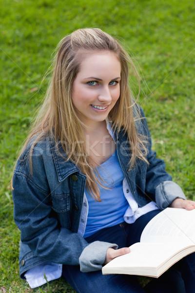 Mulher jovem olhando câmera livro sessão Foto stock © wavebreak_media