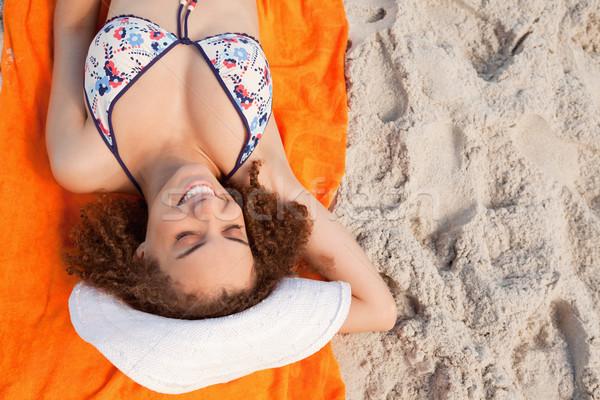 Overhead view of a young woman sunbathing while lying on her orange beach towel Stock photo © wavebreak_media